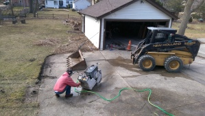 Next, Dennis unloads his bobcat and connects the hose to his concrete saw. The area of concrete just beyond him is what will be removed.